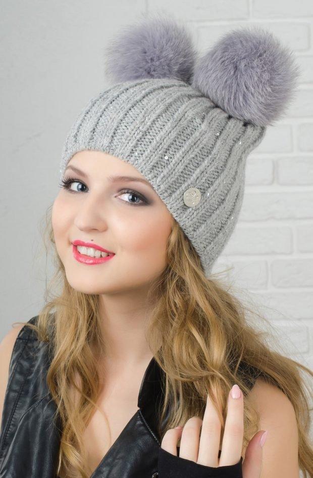 модные головные уборы осень зима 2019 2020: светло-серая вязанная шапка с двумя помпонами