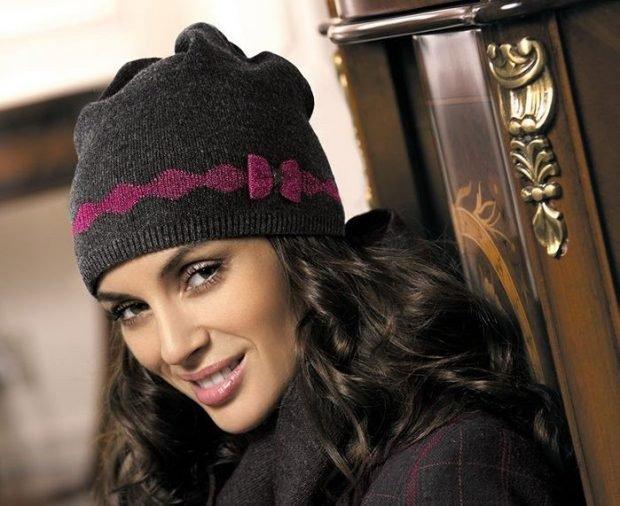 модные головные уборы осень зима 2020 2021: темная вязанная шапка с розовым бантом