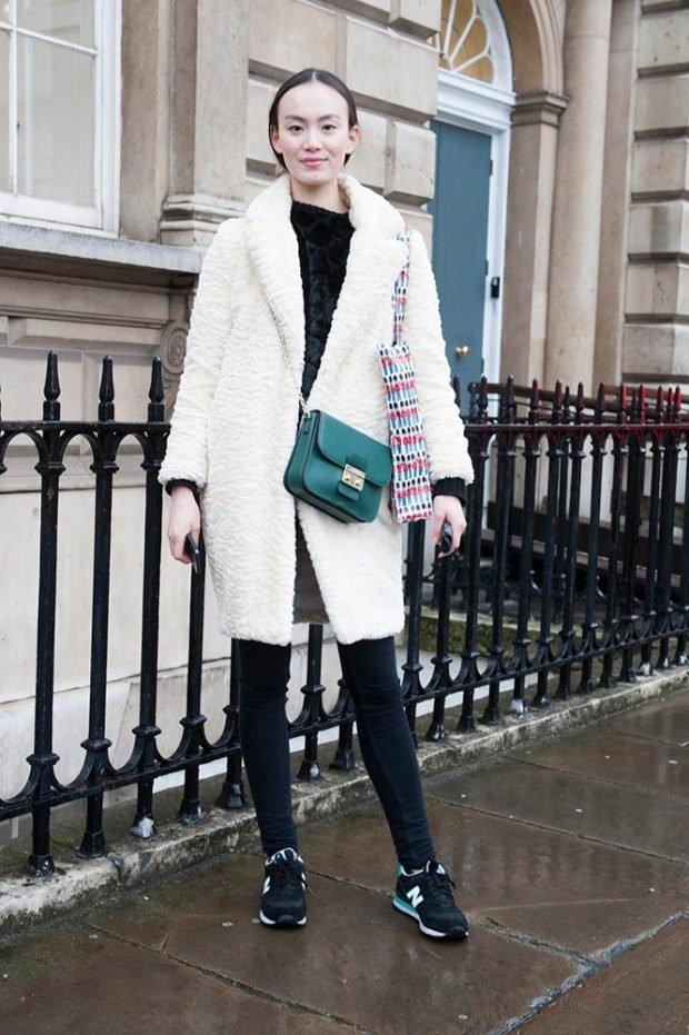 белое пальто с черными брюками и зеленой сумкой