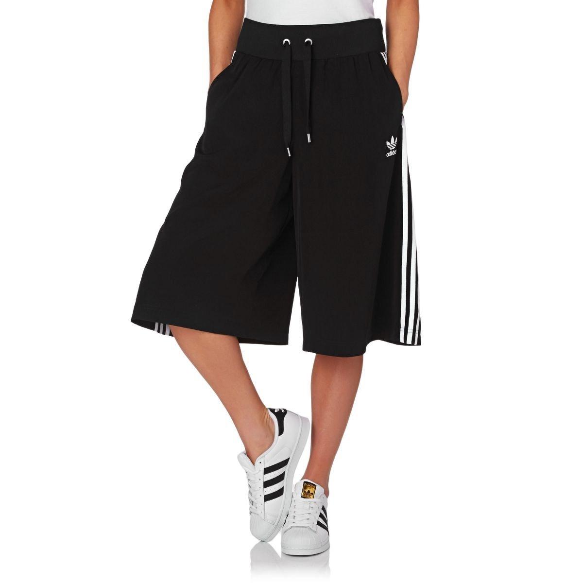 черные спортивные брюки-кюлоты и белые кроссовки
