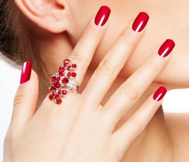 кольцо на указательном пальце с красными камнями